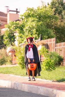 Kleiner junge im kostüm des halloween-teufels, der korb mit leckereien hält, während auf der straße gegen landhaus in natürlicher umgebung steht