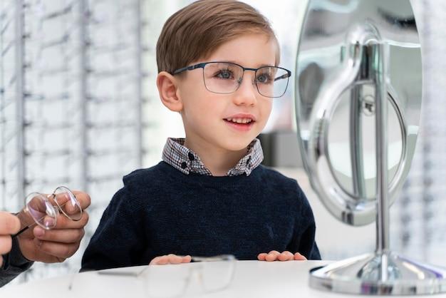 Kleiner junge im laden, der brille anprobiert