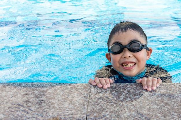 Kleiner junge im pool schwimmen.