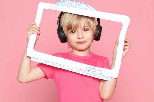 Kleiner junge im rosa t-shirt und in den schwarzen kopfhörern, die musik mit papierbildschirm hören