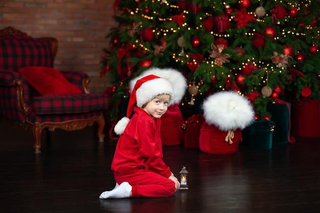 Kleiner junge im roten hut santa nahe weihnachtsbaum