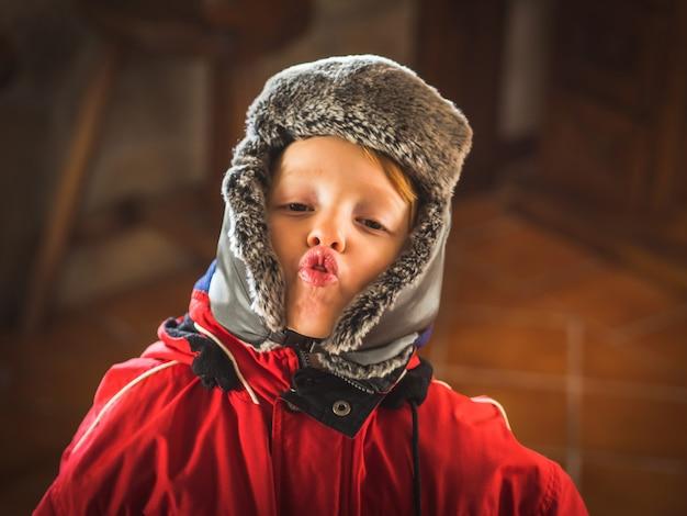 Kleiner junge im schneeanzug, der lustige ausdrücke macht
