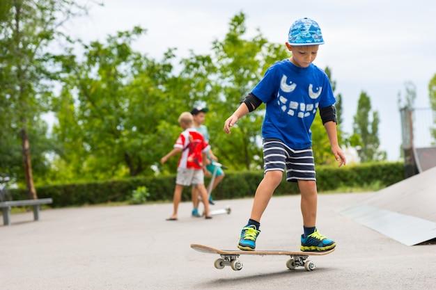 Kleiner junge im skatepark, der mit seinem skateboard spielt und seine bewegungen übt, während andere kinder im hintergrund spielen