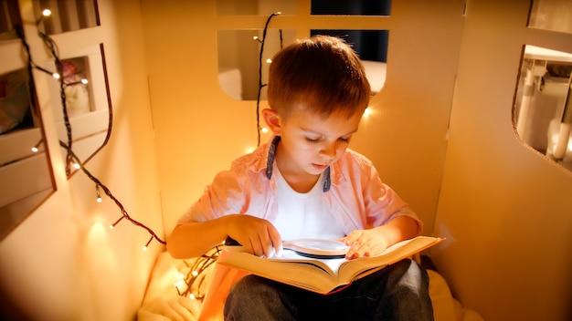 Kleiner junge im spielzeughaus mit hellen girlanden, die nachts buch lesen. konzept der kindererziehung und des lesens in der dunkelkammer.