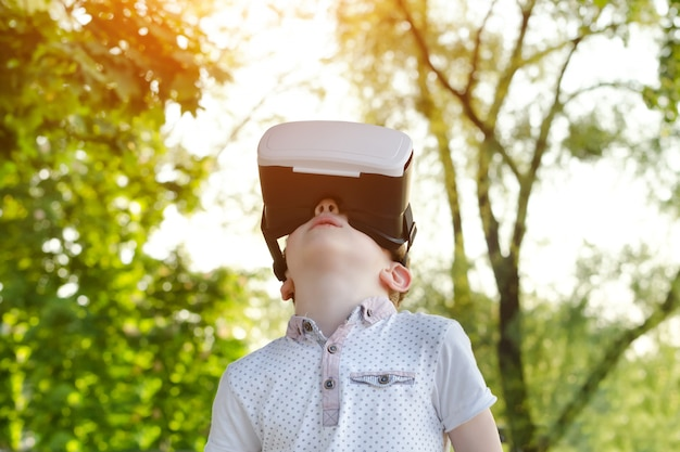 Kleiner junge im sturzhelm der virtuellen realität, der oben schaut