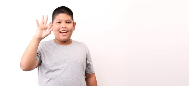 Kleiner junge im t-shirt, das ok-geste auf weißem hintergrund zeigt.