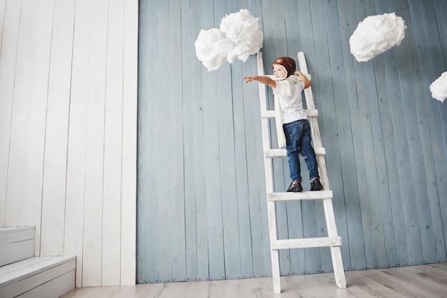 Kleiner junge im versuchshut, der auf der leiter in steht. erreiche den himmel. berühre die wolken