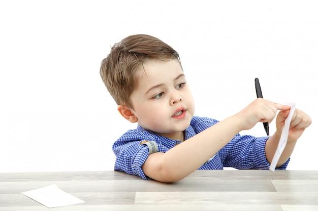 Kleiner junge im vorschulalter zeigt einen zettel
