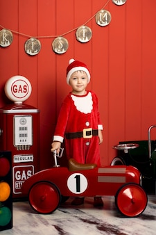 Kleiner junge im weihnachtsmann-kostüm reitet ein spielzeugrotauto. glückliche kindheit. heiligabend.
