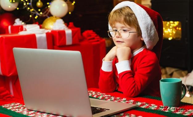 Kleiner junge im weihnachtsmannanzug sitzt vor dem laptop