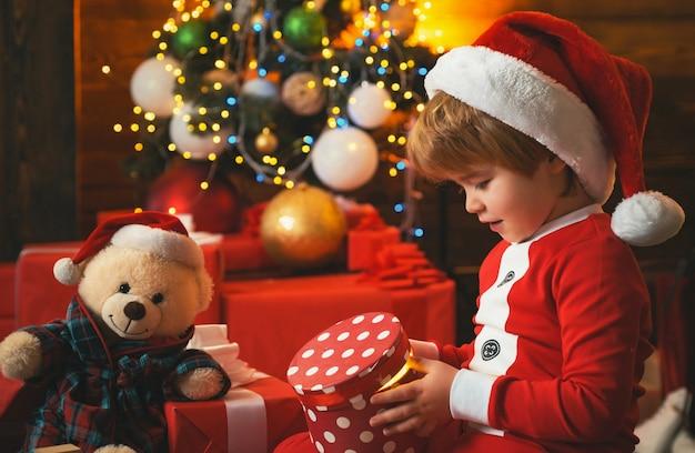 Kleiner junge im weihnachtsmannanzug spielt mit seinen spielsachen in der nähe des kamins