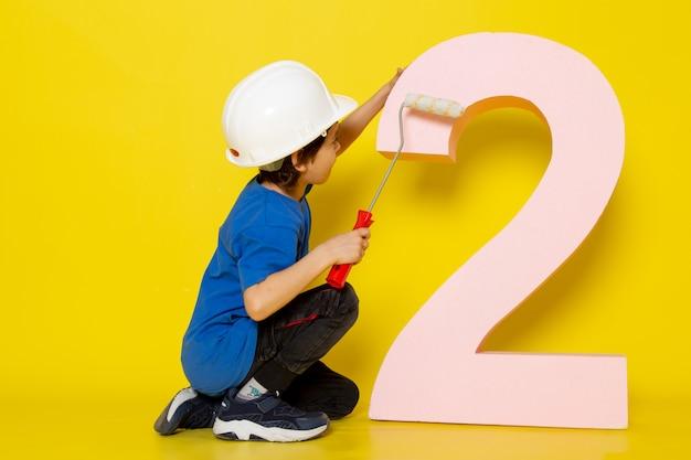 Kleiner junge im weißen helm des blauen t-shirts um zahlfigur auf gelber wand