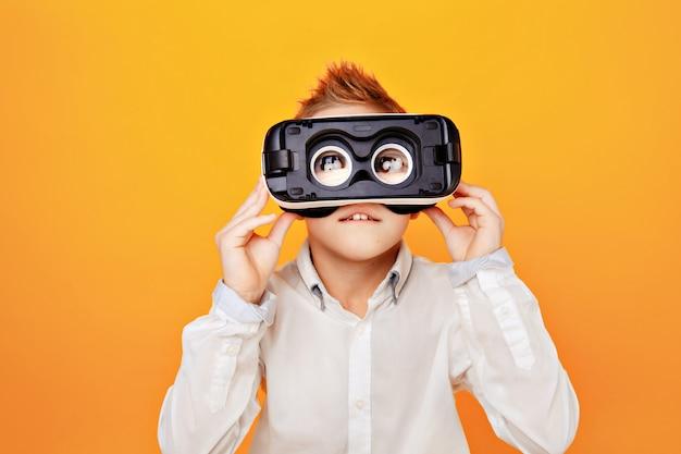 Kleiner junge im weißen hemd, das kamera durch den kopfhörer der virtuellen realität lokalisiert betrachtet