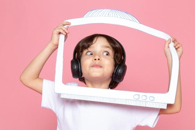 Kleiner junge im weißen t-shirt und in den schwarzen kopfhörern, die musik mit papierbildschirm hören