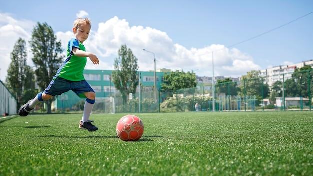 Kleiner junge in blauer und grüner form, der fußball auf offenem feld im hof spielt, ein junger fußballspieler