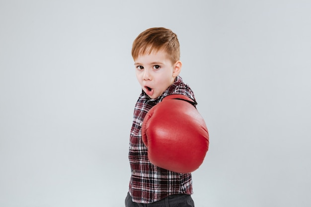 Kleiner junge in boxhandschuhen, der über weiße wand steht und kämpft