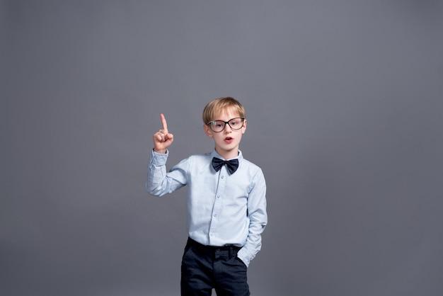 Kleiner junge in den gläsern, die auf grau aufwerfen