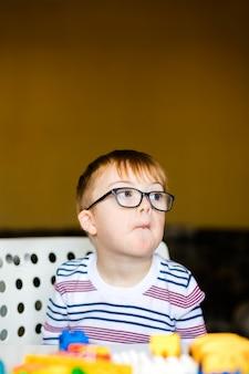 Kleiner junge in den gläsern mit der syndromdämmerung, die mit bunten ziegelsteinen spielt