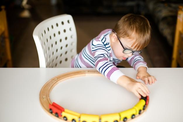 Kleiner junge in den gläsern mit der syndromdämmerung, die mit hölzernen eisenbahnen spielt