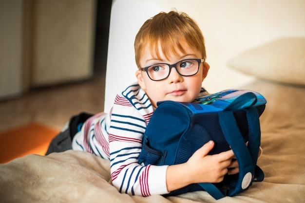 Kleiner junge in den gläsern mit der syndromdämmerung, die mit rucksack spielt