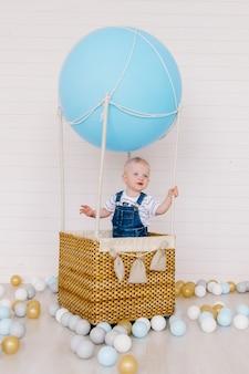 Kleiner junge in den jeans auf einem blauen ballon auf einem weißen hintergrund.