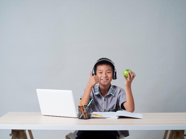 Kleiner junge in den kopfhörern, die online mit laptop lernen