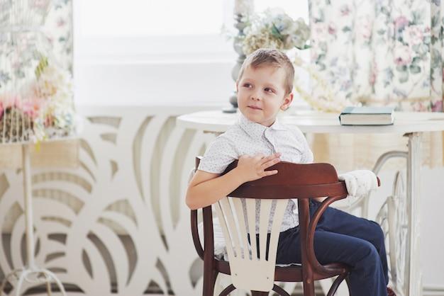 Kleiner junge in der blauen hosenjeans sitzt auf dem holzstuhl im raum. macht hausaufgaben. zurück zur schule