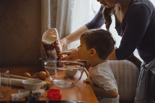 Kleiner junge in der küche hilft mama beim kochen. das kind ist am kochen beteiligt.