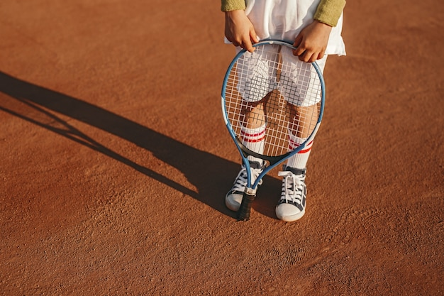 Kleiner junge in der sportbekleidung, die schläger auf tennisplatz hält