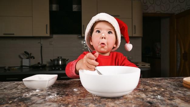 Kleiner junge in der weihnachtsmütze kocht in der küche.