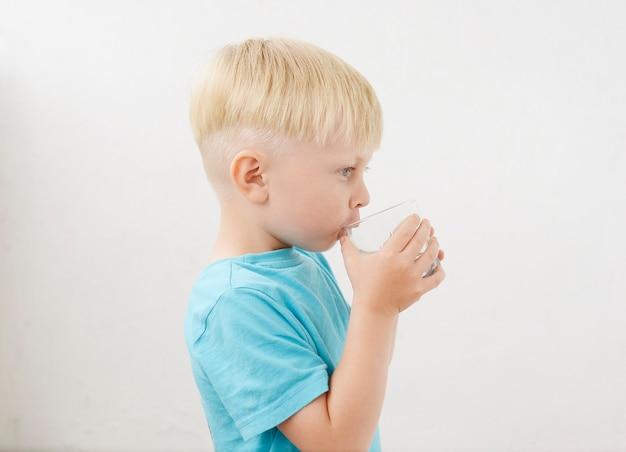 Kleiner junge in einem blauen t-shirt trinkt wasser