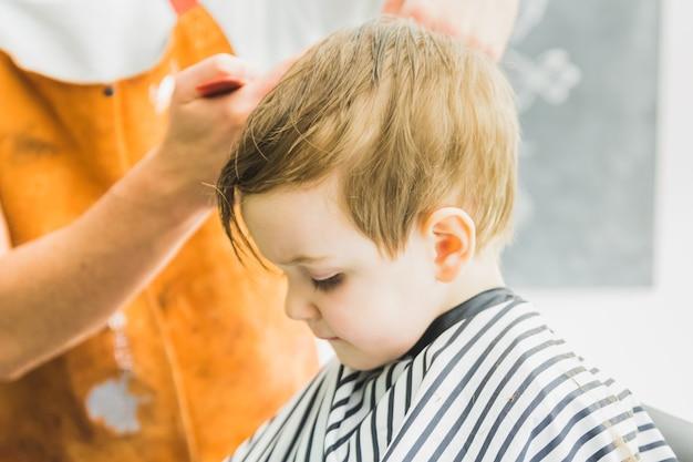Kleiner junge in einem friseursalon