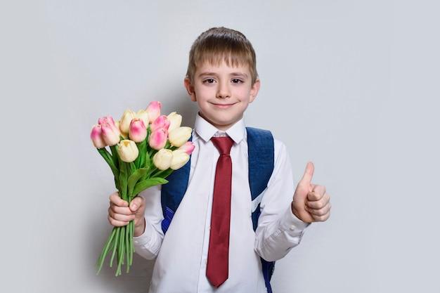 Kleiner junge in einem hemd mit der bindung und schultasche, die tulpen halten und zeigt sich daumen