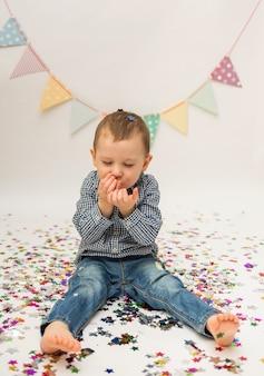 Kleiner junge in einem hemd und in jeans bläst konfetti von seinen händen auf einem weißen hintergrund