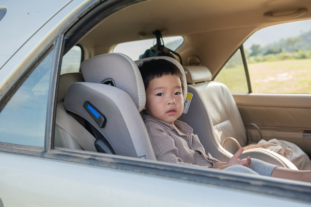 Kleiner junge in einem kindersitz, der geduldig auf der rückseite eines autos sitzt.