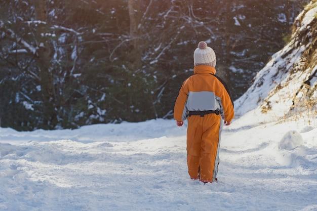 Kleiner junge in einem orangefarbenen overall auf schnee stehen