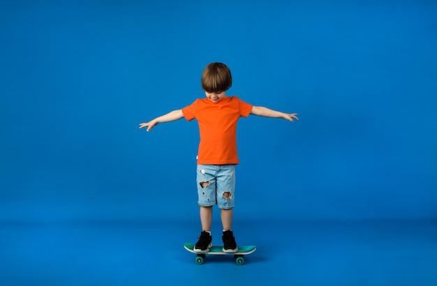 Kleiner junge in einem orangefarbenen t-shirt und jeansshorts reitet ein skateboard auf einer blauen oberfläche mit platz für text
