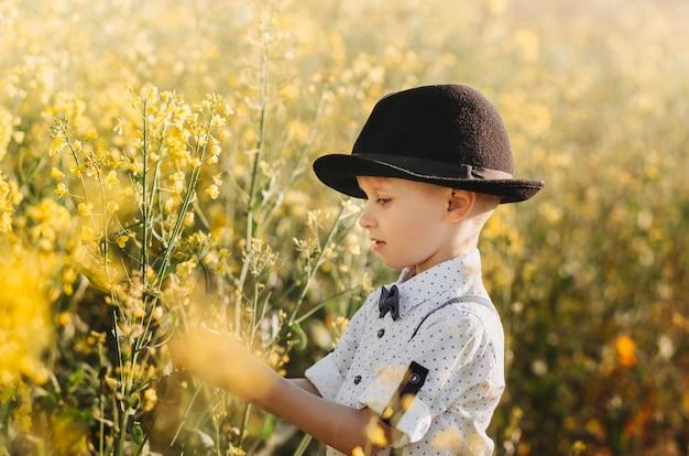 Kleiner junge in einem rapsfeld mit blüte