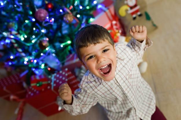 Kleiner junge in einem raum für weihnachten dekoriert
