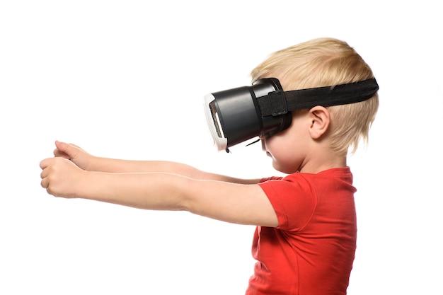 Kleiner junge in einem roten hemd erlebt virtuelle realität, die hände vor ihm hält. auf weiß isolieren. technologiekonzept