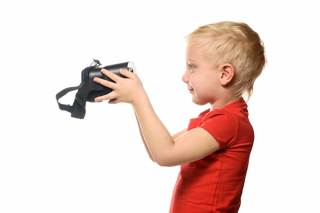 Kleiner junge in einem roten hemd hält eine virtuelle realität.