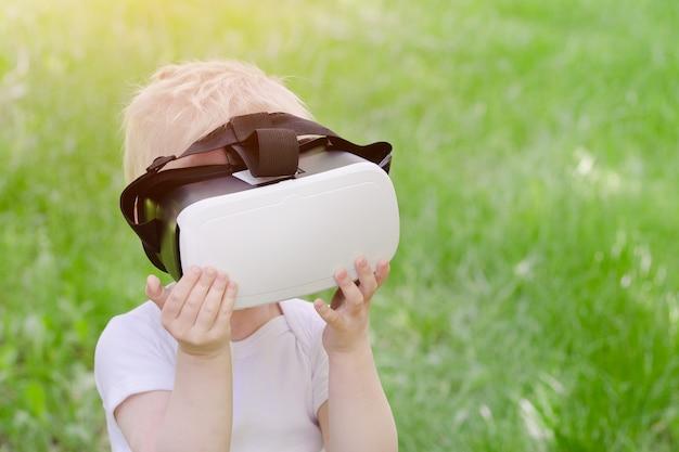 Kleiner junge in einem sturzhelm der virtuellen realität auf einem hintergrund des grünen grases