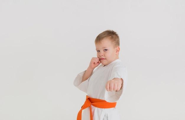 Kleiner junge in einem weißen kimono an einer weißen wand