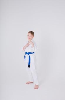 Kleiner junge in einem weißen kimono steht auf einer weißen wand