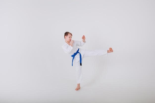 Kleiner junge in einem weißen kimono übt schläge auf eine weiße wand
