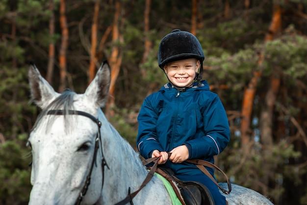 Kleiner junge in einer jockeymütze auf einem weißen erwachsenen pferd in der natur. jockey, hippodrom, reiten.