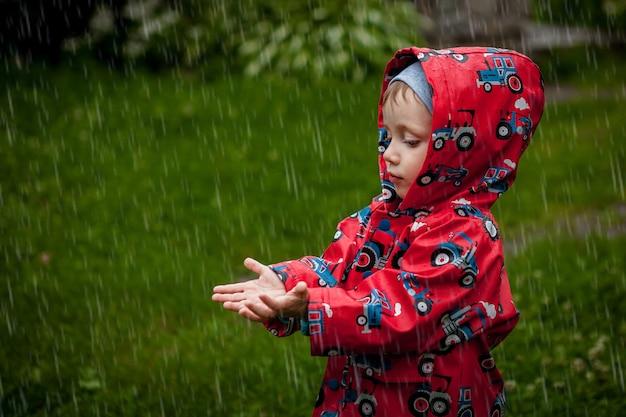 Kleiner junge in einer wasserdichten jacke in traktoren fängt den regen. kind, das spaß draußen in der sommerdusche hat