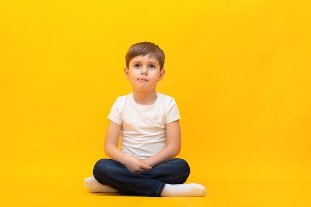 Kleiner junge in jeans und einem weißen t-shirt sitzt auf einer isolierten gelben wand