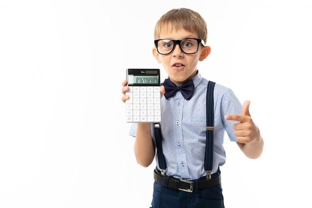 Kleiner junge in schwarzer brille mit transparenter brille, blauem hemd, klimmzügen, blauen hosen zeigt auf taschenrechner