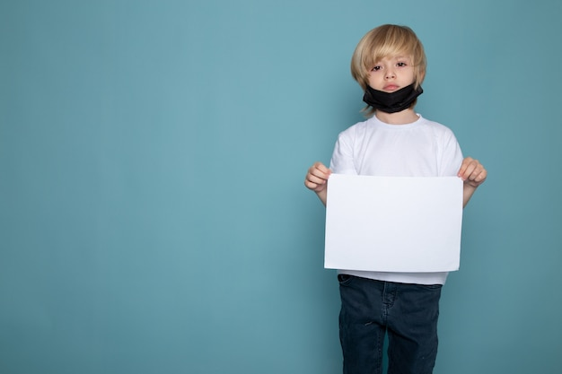 Kleiner junge in schwarzer schutzmaske gegen coronavirus mit leerem rohling auf seinen händen auf blauem schreibtisch